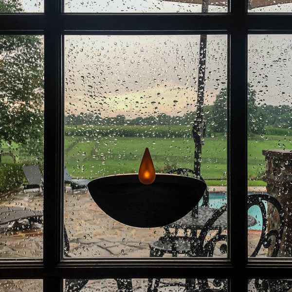 Enlite10 candle adhered on window on rainy day
